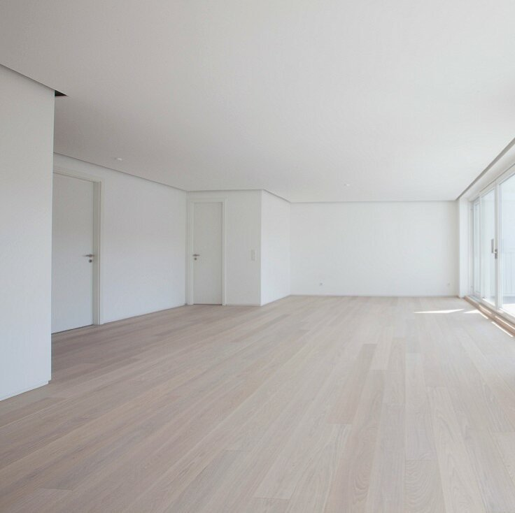 11426708-Spacious-empty-room-in-apartment-with-laminate-floor-white-walls-floor-to-ceiling-windows